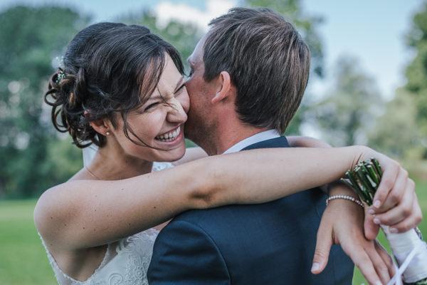 Hochzeit in Deggendorf, Paarshooting, Braut umarmt den bräutigam und lacht dabei