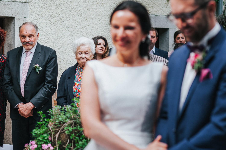 freie Trauung auf Gut Aichet, die Oma schaut stolz und zufrieden zu der Braut