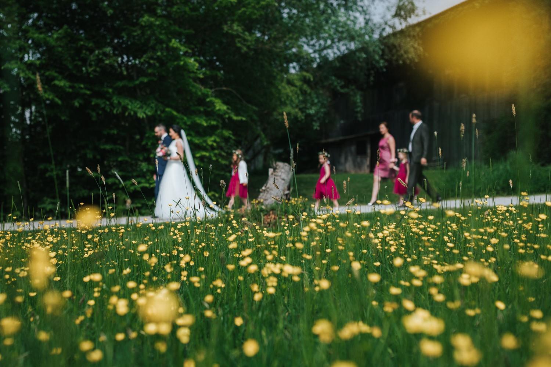 freie Trauung auf Gut Aichet, das Brautpaar und die Gäste laufen an einer Wiese entlang