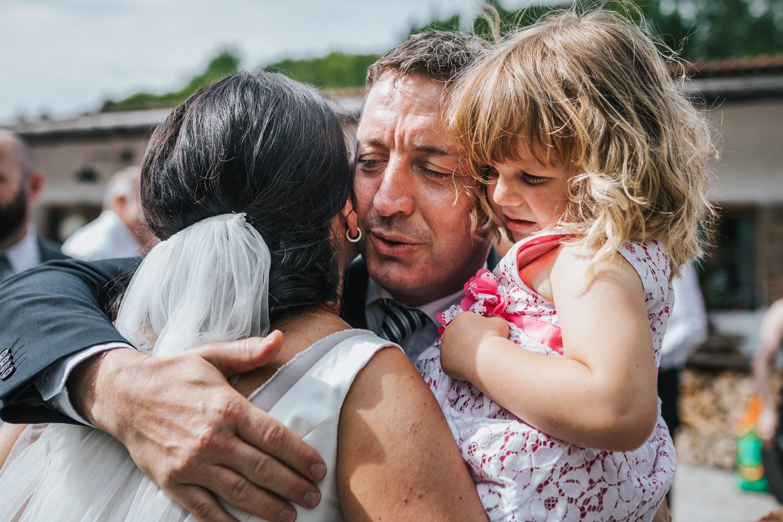 freie Trauung auf Gut Aichet, Braut umarmt einen Gast, seine Tochter ist nicht begeistert