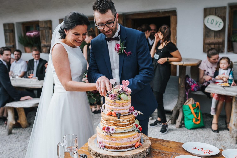 freie Trauung auf Gut Aichet, das Brautpaar schneidet die Hochzeitstorte an