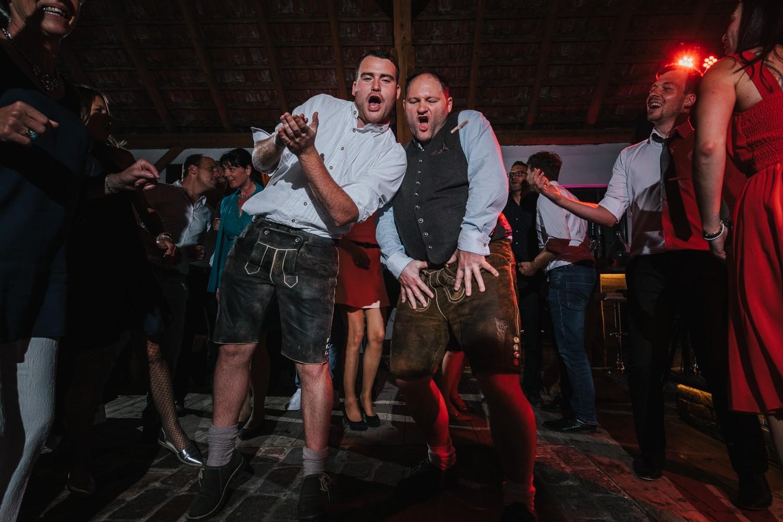 freie Trauung auf Gut Aichet, 2 Männer in Tracht tanzen ausgelassen
