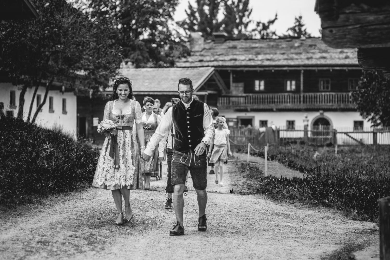 Hochzeit im Museumsdorf Tittling, Paar in Tracht läuft an Spitze von Hochzeitsgesellschaft