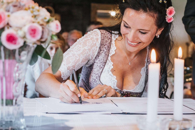 Hochzeit im Museumsdorf Tittling, Braut unterschreibt im Standesamt