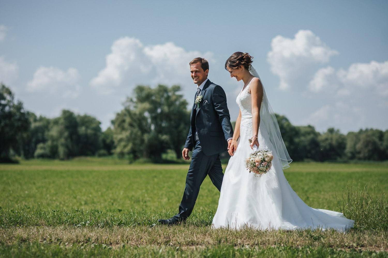 Hochzeit in Deggendorf, Paarshooting am Donauufer, Brautpaar läuft lachend einen Weg entlang