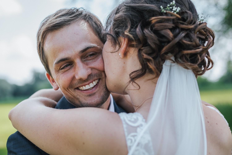 Hochzeit in Deggendorf, Paarshooting am Donauufer, Braut küsst den Bräutigam