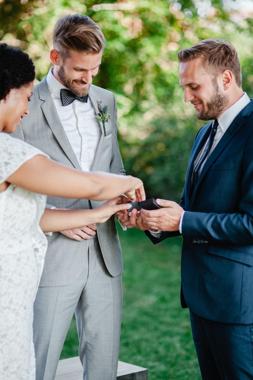 Hochzeit in Dobbrikow, freie Trauung, Brautpaar und Trauzeuge bei der Ringübergabe