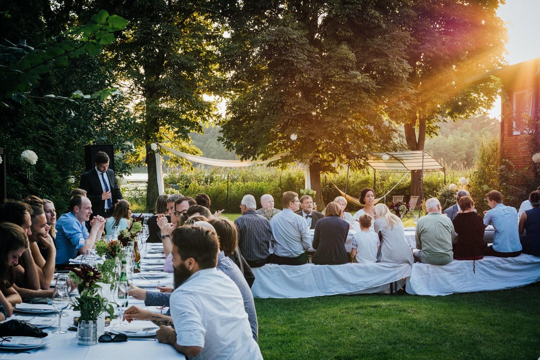 Hochzeit in Dobbrikow, die Gäste sitzen bei Sonnenuntergang an ihren Tischen und unterhalten sich