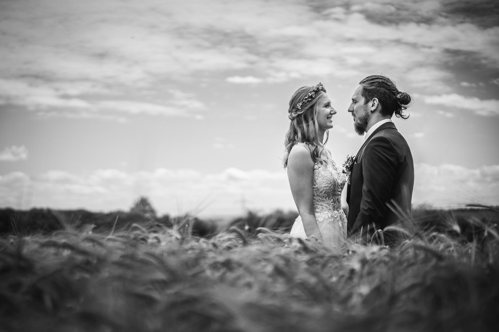 Hochzeit in Fürstenzell, Brautpaar steht auf einem Feldweg und lächelt sich an