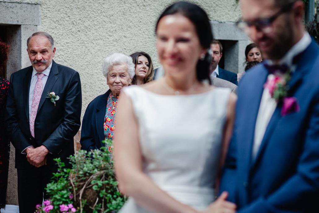 Hochzeit im Gut Aichet bei Passau, freie Trauung, Großmutter schaut zufreiden und wohlwollend zur Braut