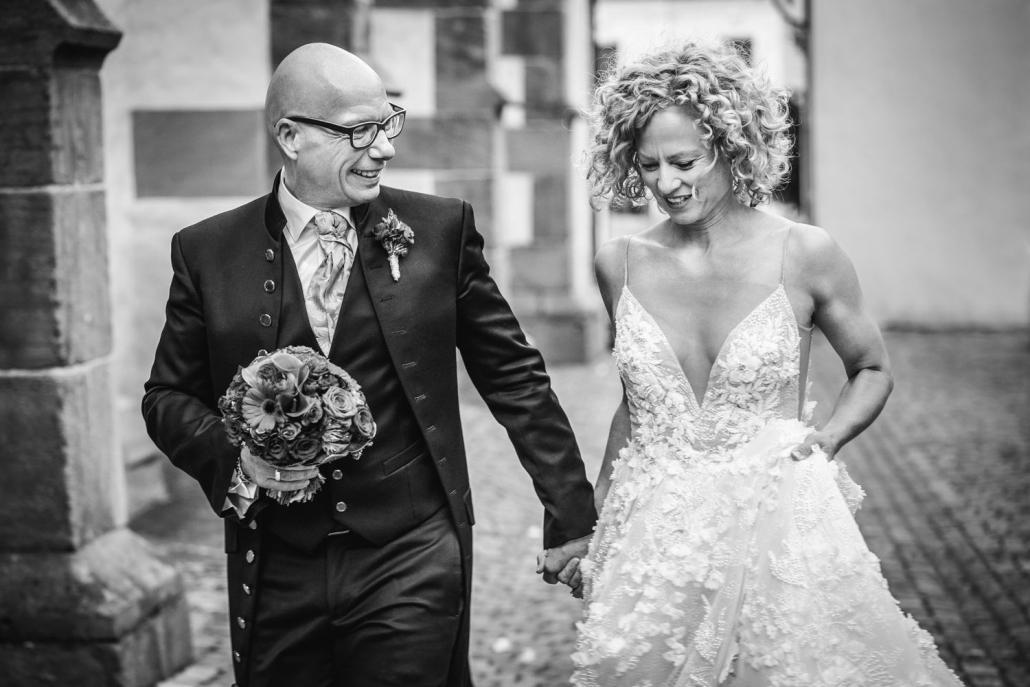 kirchliche Hochzeit in Deidesheim, Brautpaar läuft der Kirche entlang