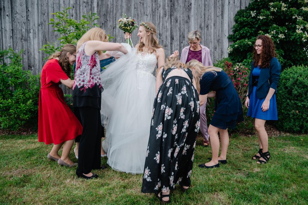 Hochzeit in Fürstenzell und Untersimbach, Paarshooting, die weiblichen Gäste richten das Kleid der Braut