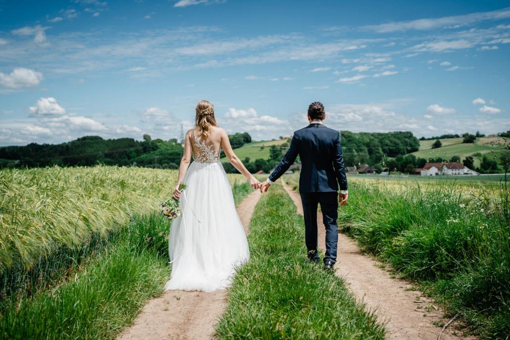 Hochzeit in Fürstenzell und Untersimbach, Paarshooting, Brautpaar läuft Hand in Hand über Feldweg