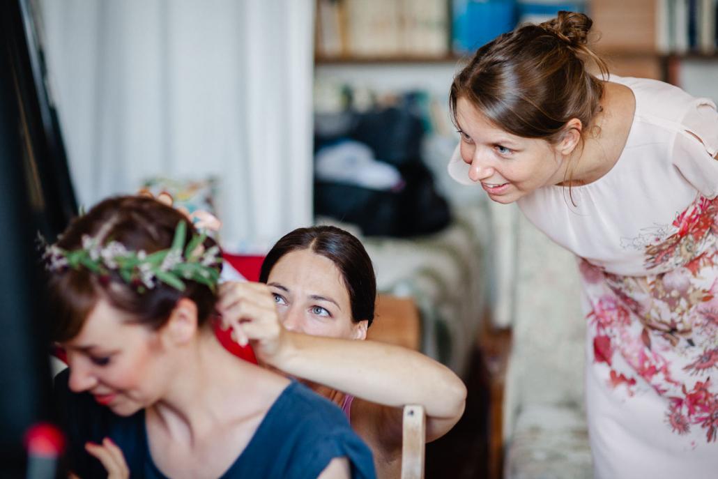 Hochzeit im Kulturgut Wrechen, Trauzeugin schaut der Braut beim Ankleiden zu