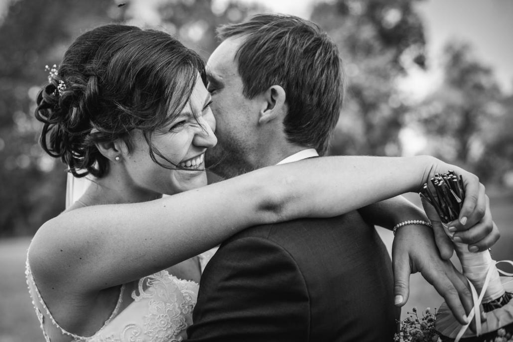 kirchliche Hochzeit in Ortenburg, Brautpaar umarmt sich, die Braut lächelt aus vollem Herzen