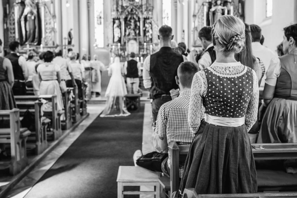 kirchliche Hochzeit in Bad Füssing, Hochzeitsgast in Tracht schaut sich die Trauung an