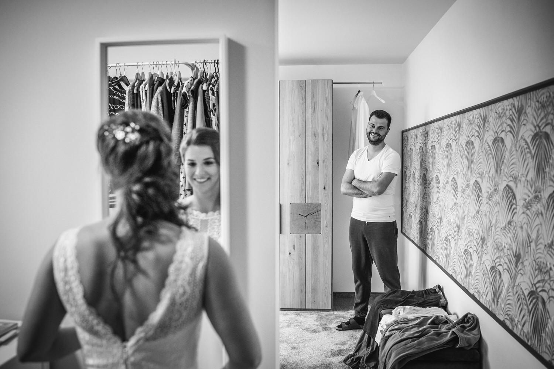 Hochzeit in Bad Birnbach, Getting Ready in Osterhofen, Braut betrachtet sich im Spiegel, Bräutigam blickt zu ihr