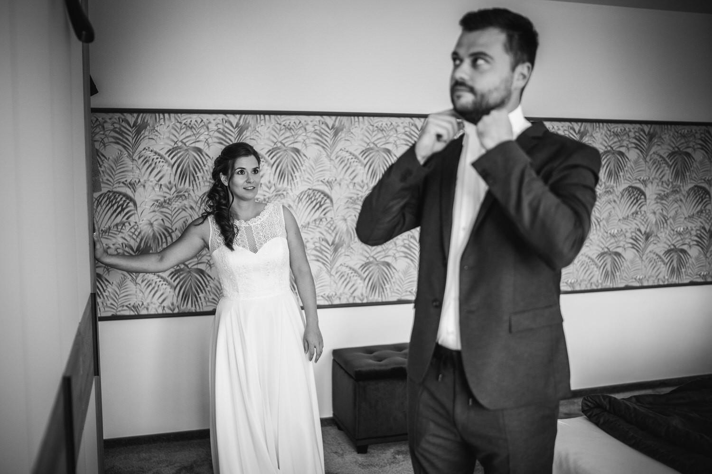 Hochzeit in Bad Birnbach, Getting ready in Osterhofen, Braut schaut Bräutigam beim Ankleiden zu