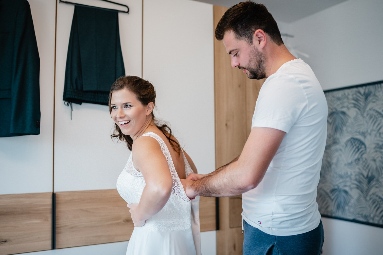 Hochzeit in Bad Birnbach, Getting Ready in Osterhofen, Bräutigam hilft Braut beim Anzeihen des Kleides
