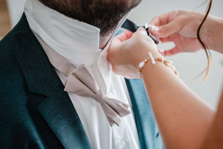 Hochzeit in Bad Birnbach, Getting Ready in Osterhofen, Braut bindet Bräutigam die Fliege um