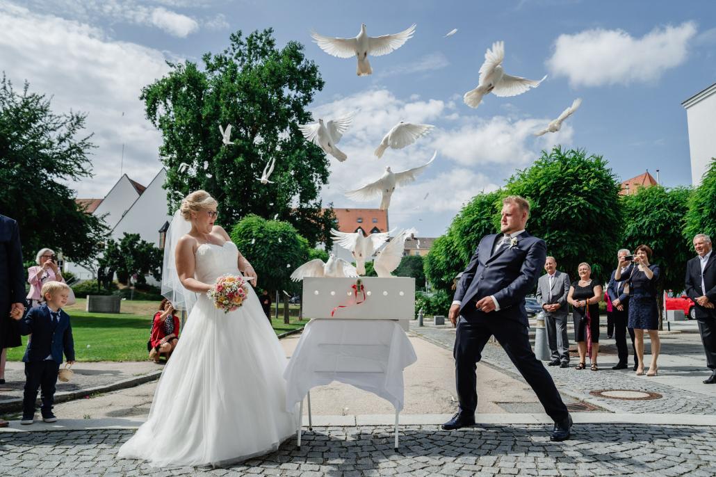 Hochzeit in Fürstenzell, Brautpaar weicht den aufsteigenden Tauben aus