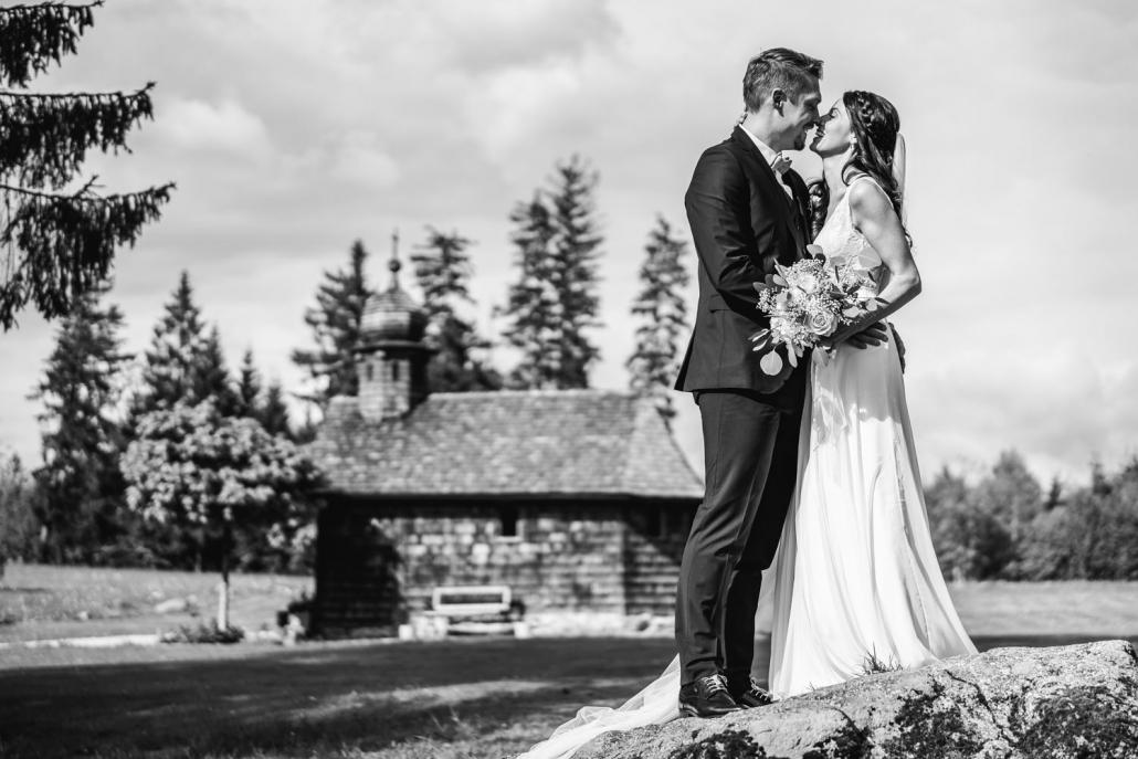 Hochzeit Gutsalm Harlachberg, Paarshooting, Paar steht vor Holzkirche