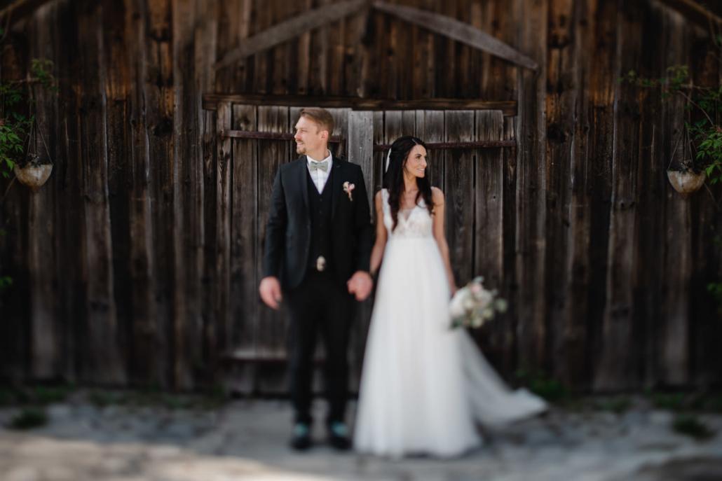 Hochzeit Gutsalm Harlachberg, Paarshooting, das Paar vor einer Scheunentür