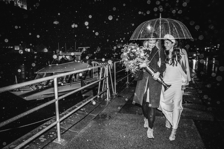 Hochzeit auf dem Cabrioshiff MS Sunliner, Passau, Braut läuft Arm in Arm mit ihrer Freundin durch den Regen