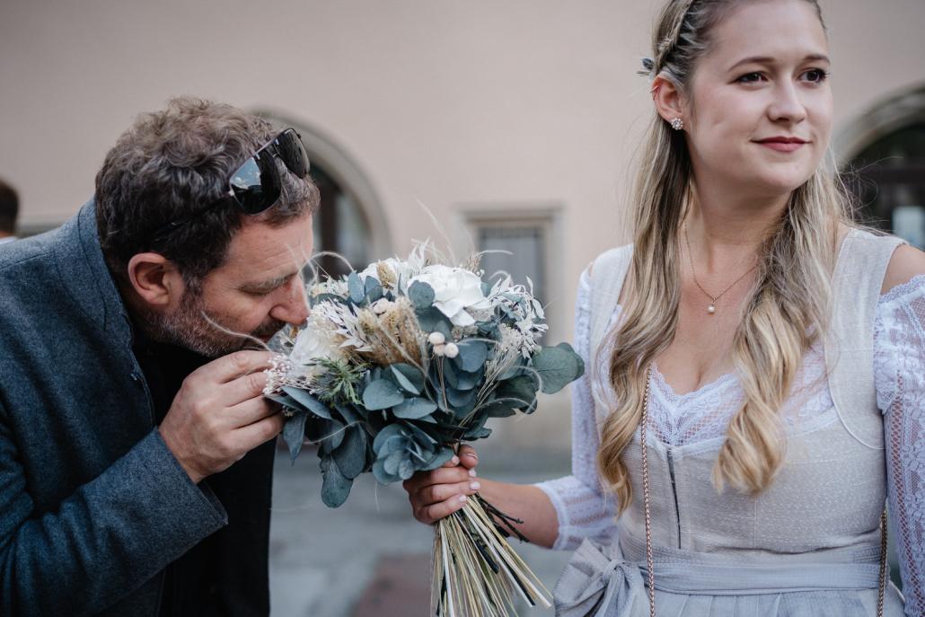Hochzeit im Standesamt Passau, Gast der Trauung riecht am Brautstrauß