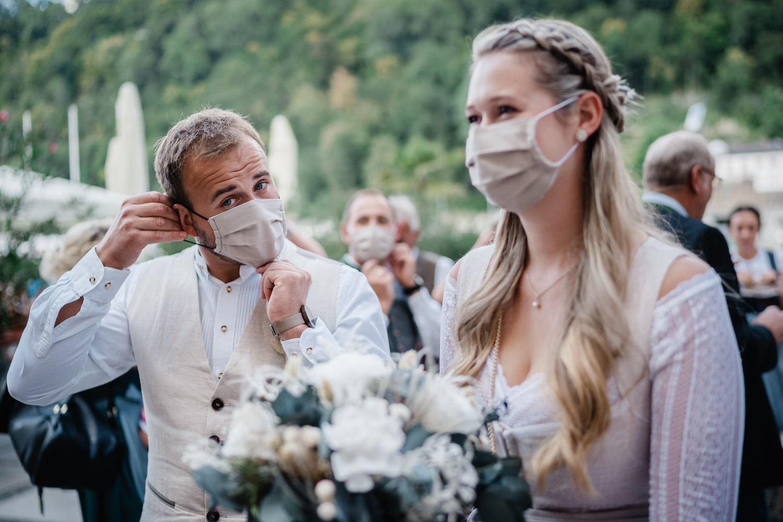 Hochzeit im Standesamt Passau, Brautpaar setzt sich die Maske auf