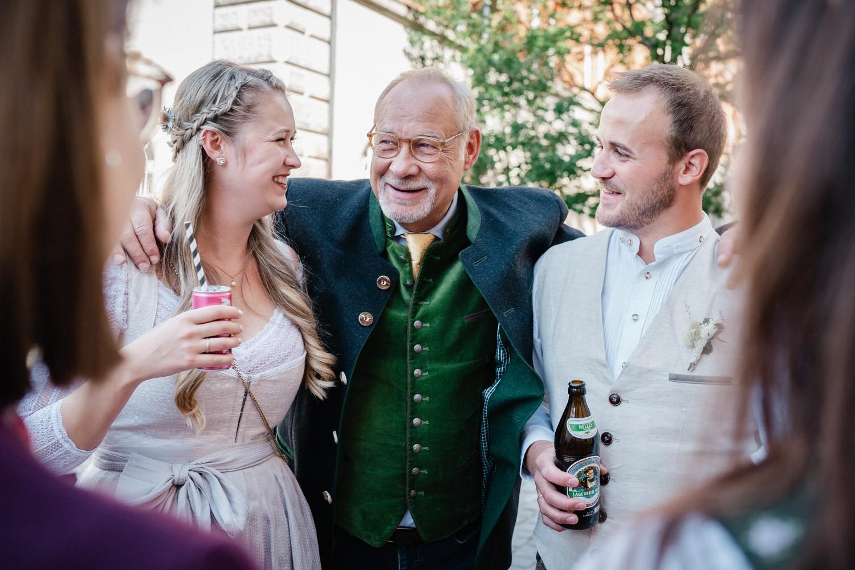 Hochzeit im Standesamt Passau, der Brautvater umarmt das Brautpaar
