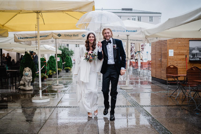 Hochzeit im kleinen Rathaussaal Passau, BRautpaar läuft durch nach der Trauung durch den Regen