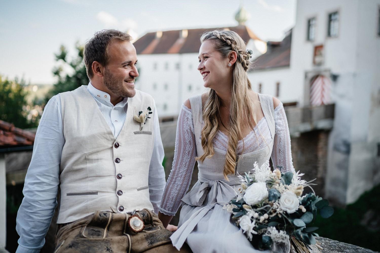 Hochzeit in der Veste Oberhaus Passau, Paarshooting, Brautpaar sitzt auf Mauer und lächelt sich an
