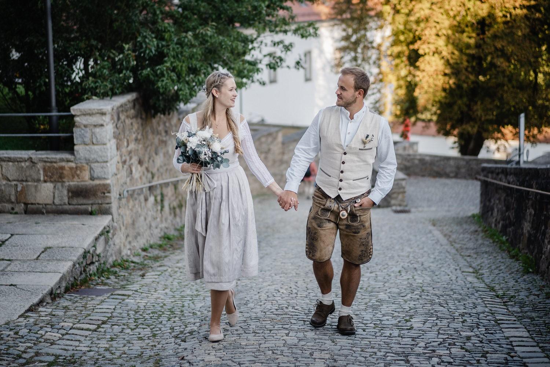 Hochzeit in der Veste Oberhaus Passau, Paarshooting, Brautpaar läuft Hand in Hand