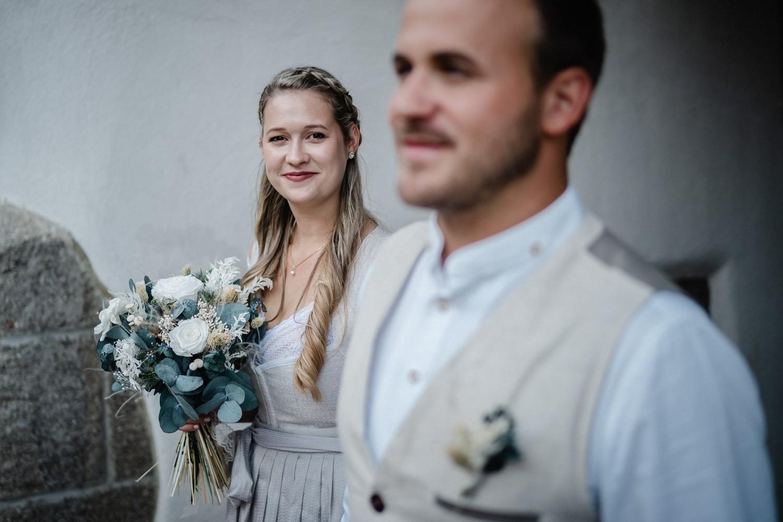 Hochzeit in der Veste Oberhaus Passau, Paarshooting, Braut schaut in die Kamera, Bräutigam ist unscharf im Vordergrund