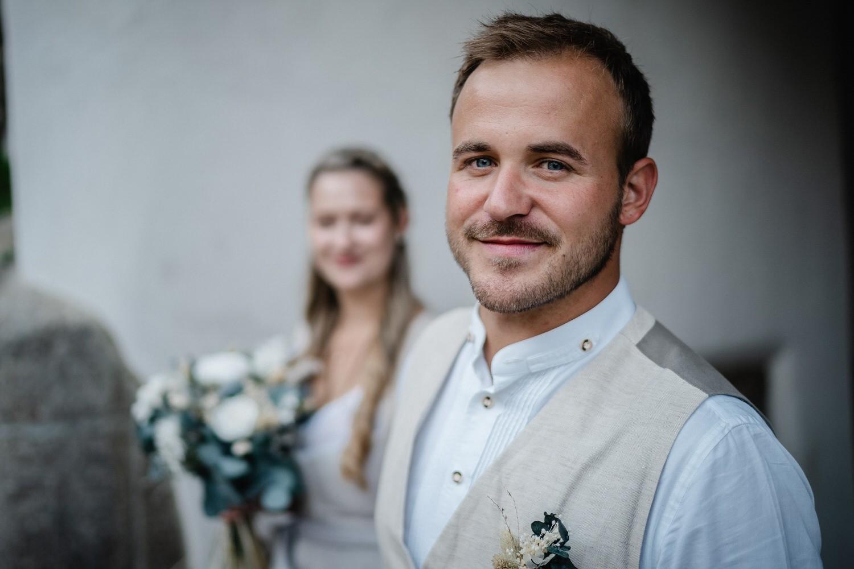 Hochzeit in der Veste Oberhaus Passau, Paarshooting, Bräutigam schaut in die Kamera, Braut ist unscharf im Hintergrund