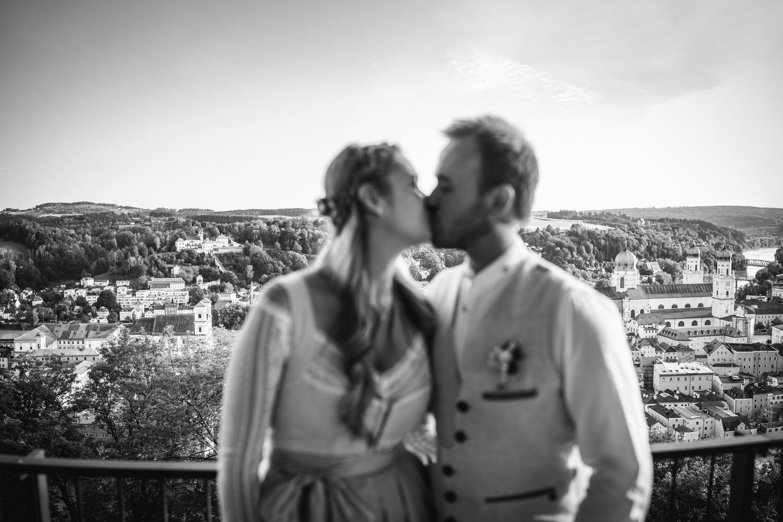Hochzeit in der Veste Oberhaus Passau, Paarshooting, Brautpaar küsst sich der Stadtkulisse Passaus