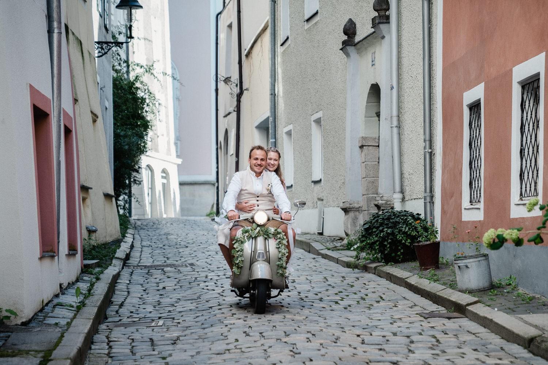 standesamtliche Hochzeit im kleinen Rathaussall Passau, Paar fährt mit altem Roller durch die Gassen von Passau