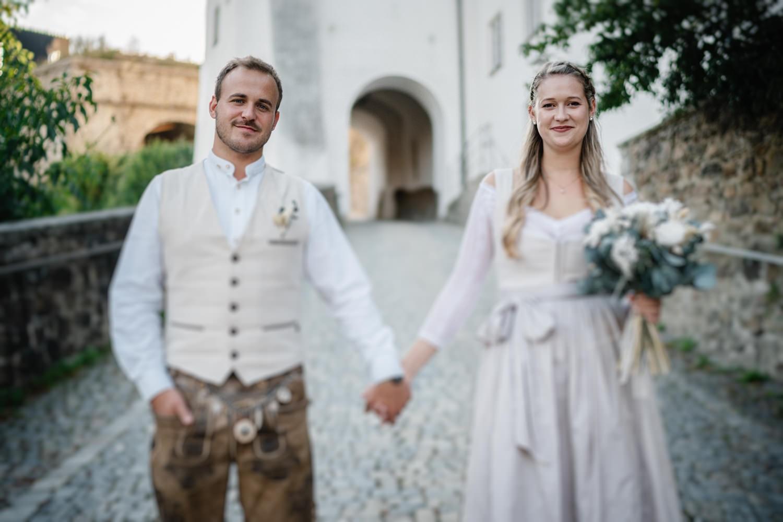 Hochzeit auf der Veste Oberhaus, Paarshooting, Braut und Bräutigam stehen frontal zur Kamera und blicken hinein