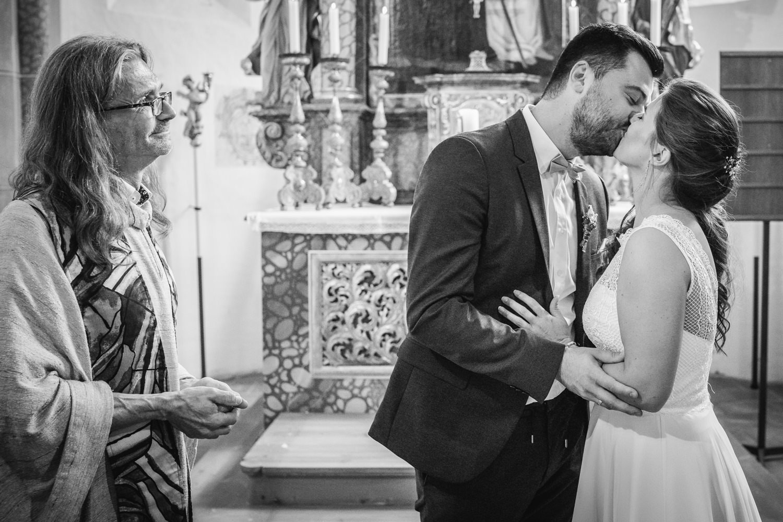 kirchliche Hochzeit in Grongörgen, Bad Birnbach, das brautpaar küsst sich, der Pfarrer schaut zu