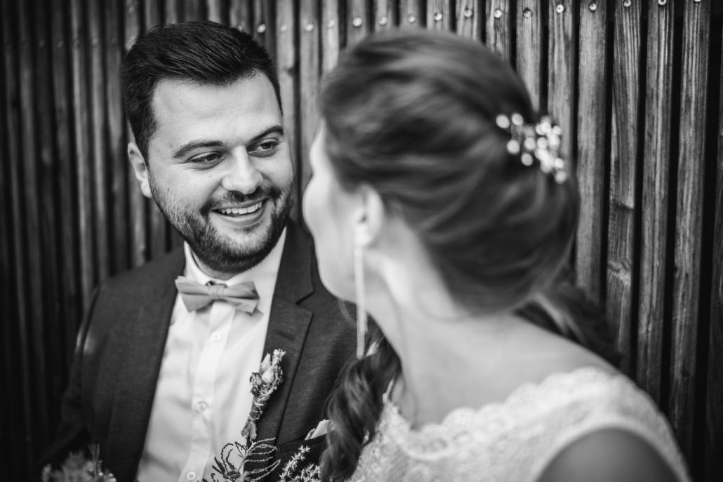 Hochzeit im Hofgut Hafnerleiten, Bad Birnbach, Paarshooting, Bräutigam schaut die Braut an und sitzt an Holzwand