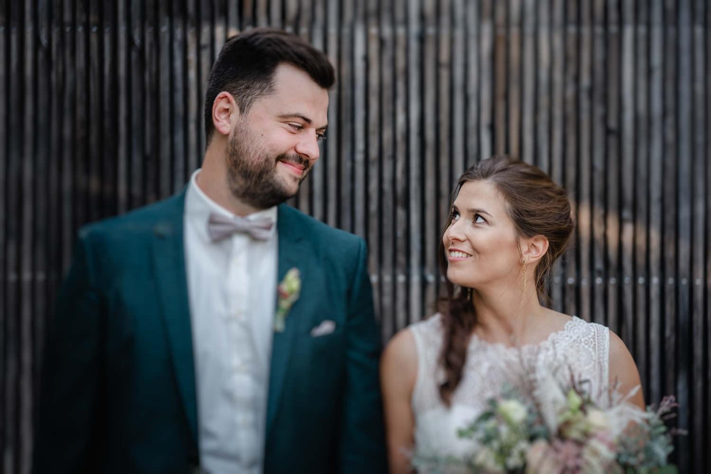 Hochzeit im Hofgut Hafnerleiten, Bad Birnbach, Paarshooting, Brautpaar steht vor Holzwand und schaut sich an