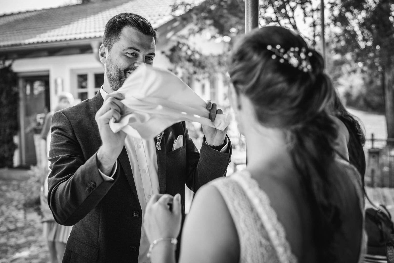 Hochzeit im Hofgut Hafnerleiten, Bad Birnbach, Bräutigam fächert der braut frische Luft zu