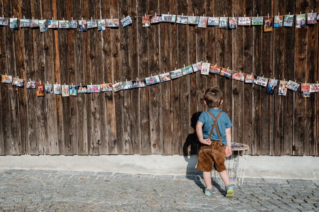 Hochzeit auf dem Rahaberghof, Oberösterreich, kleiner Junge schaut auf die Bilderwand