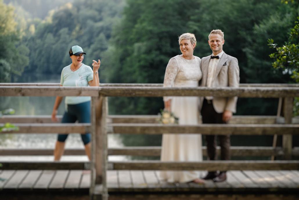 Hochzeit auf dem Rahaberghof, Oberösterreich, Paarshooting, Paar steht auf Brücke während Frau mit mahnendem Finger vorbei geht