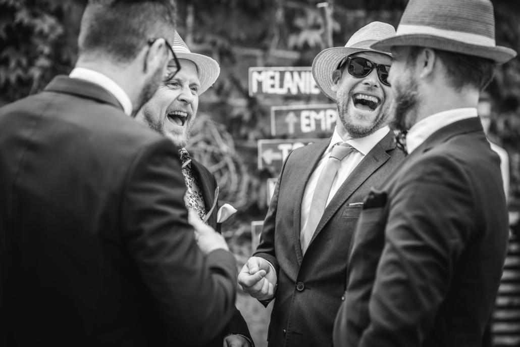 Hochzeitsreportage auf Gut Aichet, Gäste scherzen und lachen mit dem Bräutigam