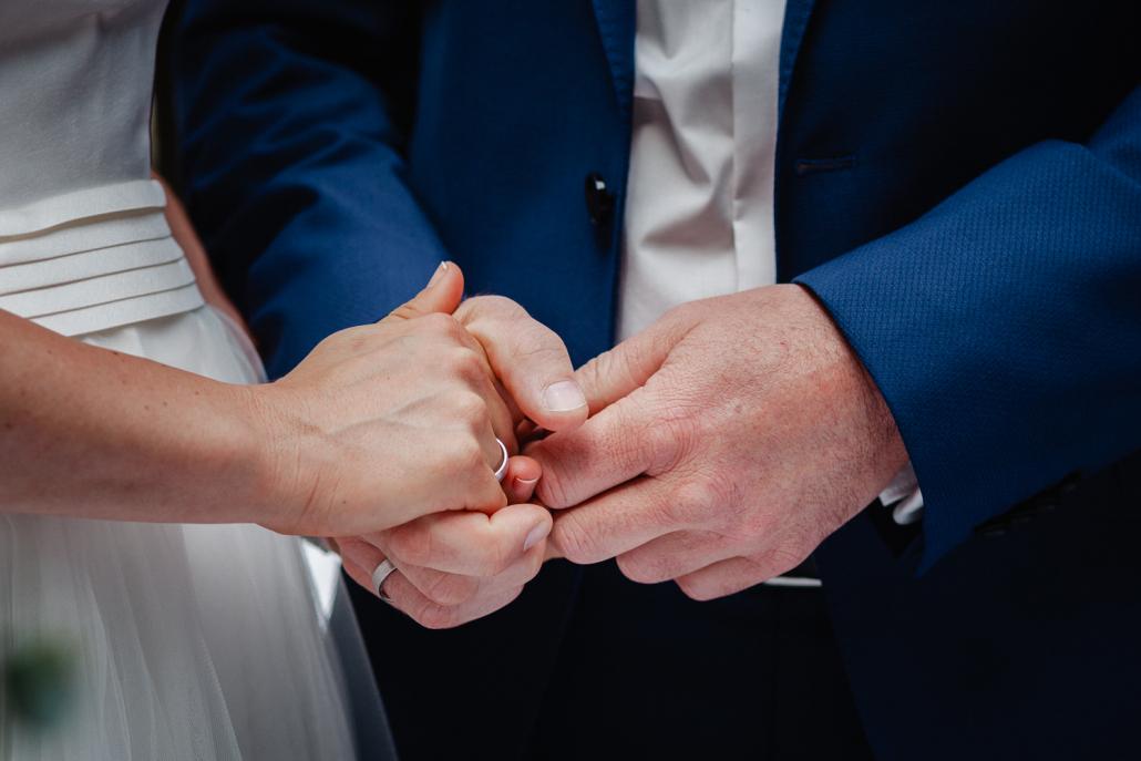 Hochzeit auf Gut Aichet, das Brautpaar hält sich an den Händen