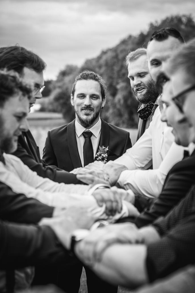 Hochzeit in Fürstenzell, der bräutigam blickt auf die männlichen gäste, die ihn in die Luft werfen wollen