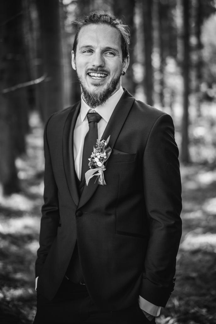 Hochzeit in Fürstenzell, Portraitaufnahme vom Bräutigam, der lächelnd an der Kamera vorbeischaut