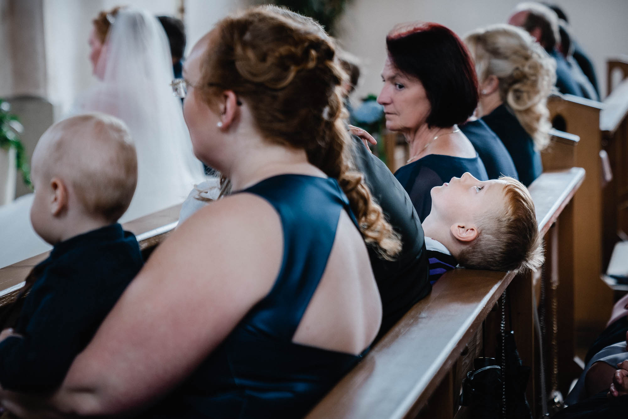 Hochzeit in Osterhofen, Junge schaut während der Trauung an die Decke